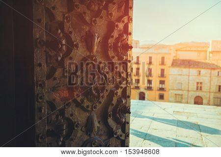 Ajar half old inlaid ornamental wrought iron door in Girona, Spain, vintage colour