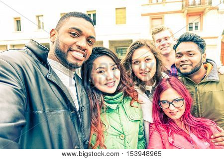 Multiracial group of friends taking selfie standing on the street at winter season - Happy students smiling at phone camera in a joyful self portrait - Concept of teenage cheerful moments together