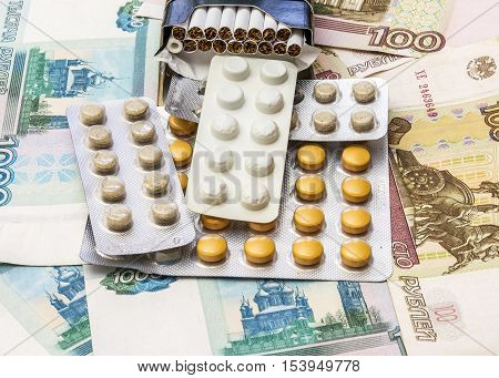 On banknotes is a pack of cigarettes and packaging of medical drugs