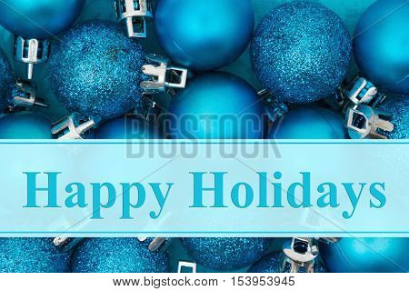 Happy Holidays greeting Some bright blue sparkle and matte Christmas ball ornaments with text Happy Holidays