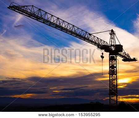 Crane silhouetted against the sunset with orange clouds HD