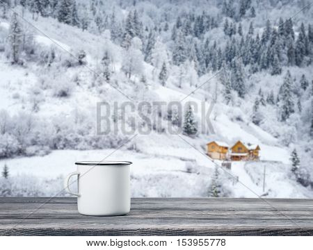 White cup of tea on wooden table against background of hotel in winter mountains