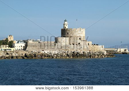 Stone Fort of St. Nicholas with the lighthouse in the harbor of Mandraki. Rhodes. Greece
