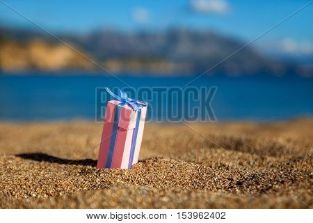 One pink gift box on a beach