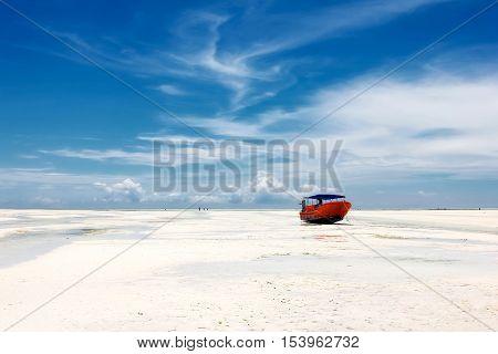 Red boat on the beach of Zanzibar on the blue sky background. Africa. Zanzibar.