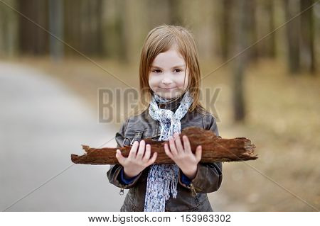 Adorable girl having fun on early spring or late autumn