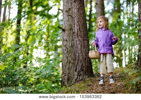 Adorable Little Girl Picking Berries In The Forest