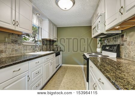 Interior Of Kitchen Room With White Cabinets, Granite Tops