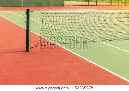 oldgreen tennis court with net pole and net with sun light
