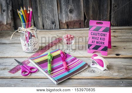 horizontal image of an assortment of school supplies like crayons books and scissors with a little sign saying