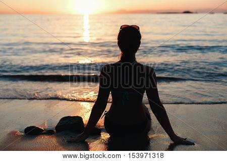 the girl on the shore of the sea sitting and watching the sunset. silhouette of girl at sunset.