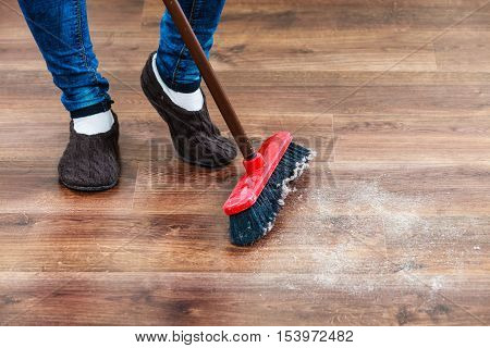 Cleanup housework concept. Closeup broom and female foots. Cleaning woman sweeping wooden floor.