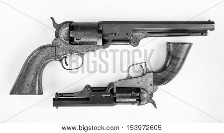 Two old western six shooter cowboy pistols in black and white.