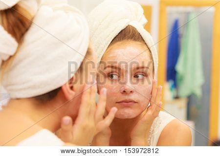 Woman Applying Mask Cream On Face In Bathroom