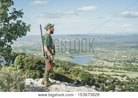 Hunter young man standing on peak mountain during hunting period - Bearded guy waiting for the pray with wonderful panoramic view background - Hunting concept - Soft desaturated warm vintage filter