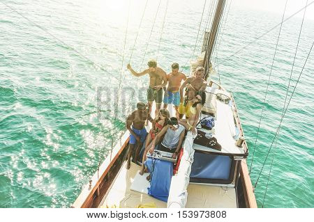 Group of young people drinking and dancig in sailing boat party with dj playing music - Top view of multiracial friends having fun in summer vacation - Main focus on dj - Warm filter with back light