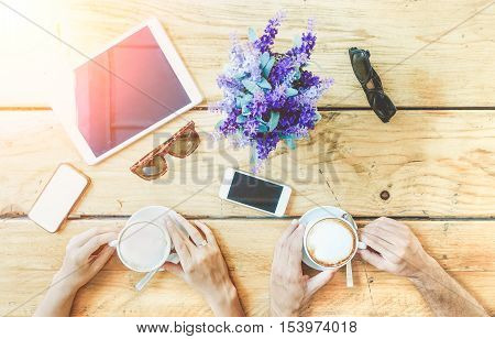 Couple of lovers drinking cappuccino at coffee bar restaurant on vacation - People hands cheering and toasting with upper view point - Coffee break concept - Soft focus on left hands - Warm filter