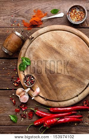 culinary background with empty cutting board, spices and ingredients