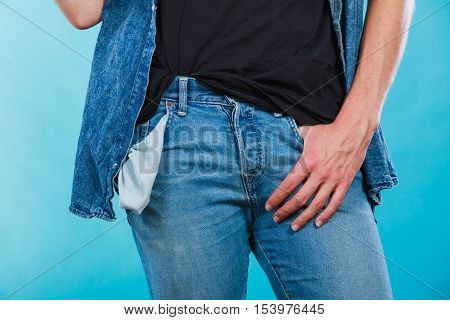 Financial difficulties bad economy no money concept. Young man student boy showing empty pockets part of body male hips wearing jeans pants