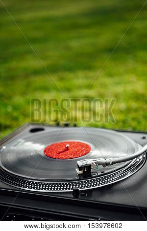 turntable with LP vinyl record against green grass background