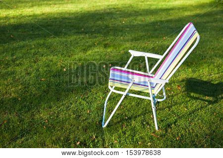 garden chair on green grass background