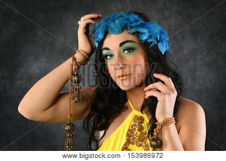 Portrait of young woman wearing blue feather crown