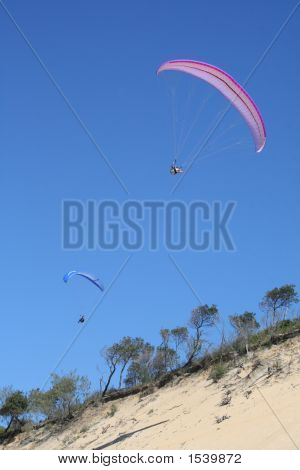 2 Paragliders Soaring Above The Beach