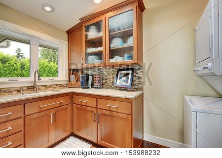 Kitchen storage combination with multicolored backsplash in the corner of kitchen room view of white laundry appliances nearby. Northwest USA