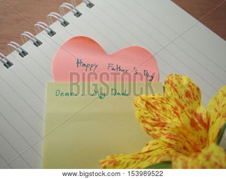 Happy father's day handwriting with sticky paper on opened notebook and handmade canna flower