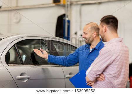 auto service, repair, maintenance and people concept - mechanic with clipboard showing side window to man or owner at car shop