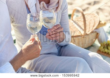family, age, holidays, leisure and people concept - close up of happy senior couple having and clinking wine glasses on summer beach