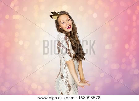 people, holidays and celebration concept - happy young woman or teen girl in party dress and golden princess crown over rose quartz and serenity lights background