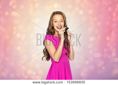 people, holidays and celebration concept - happy young woman or teen girl in pink dress and party horn or blower over rose quartz and serenity lights background