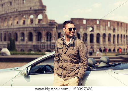 travel, tourism, road trip, transport and people concept - happy man near cabriolet car over coliseum in rome background