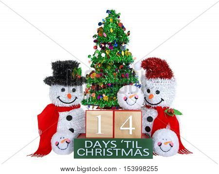 14 Days until Christmas light beech wood blocks with red trim on a green base with tinsel christmas tree mr and mrs snowman and snowball snowmen heads isolated on a white background.