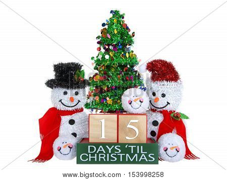 15 Days until Christmas light beech wood blocks with red trim on a green base with tinsel christmas tree mr and mrs snowman and snowball snowmen heads isolated on a white background.