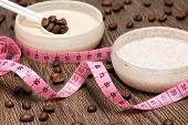 Weight loss and cellulite busting concept. Body measuring tape and anti-cellulite cosmetic products with caffeine. Shallow depth of field poster