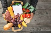 Man's hands holding paper bag of groceries with blank notebook to write your text top view with copy space poster