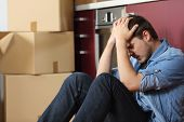 Sad evicted man worried relocating house sitting on the floor in the kitchen poster