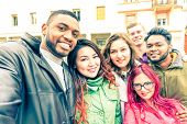 Multiracial group of friends taking selfie standing on the street at winter season - Happy students smiling at phone camera in a joyful self portrait - Concept of teenage cheerful moments together poster