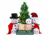 15 Days until Christmas light beech wood blocks with red trim on a green base with tinsel christmas tree mr and mrs snowman and snowball snowmen heads isolated on a white background. poster