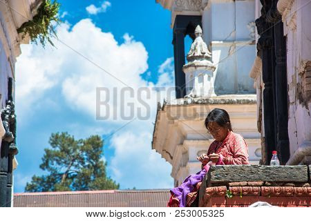 Kathmandu, Nepal - 13.04.2018: An Old Woman Sews Clothes In The Temple Complex Pesonalised 13 April