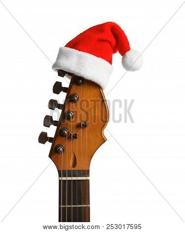 Guitar With Santa Hat On White Background. Christmas Music Concept