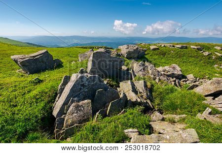Range Of Stones On The Grassy Hill. Beautiful Summer Landscape With Fluffy Clouds Above The Distant