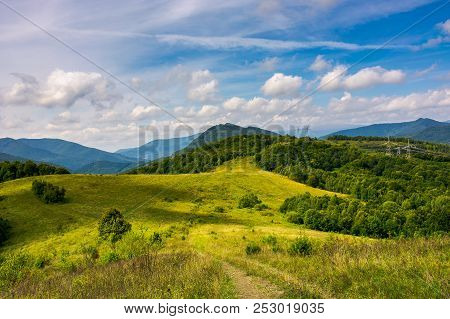 Mountainous Countryside In Early Autumn. Path Through Grassy Meadow In To The Forest On Hill. Power
