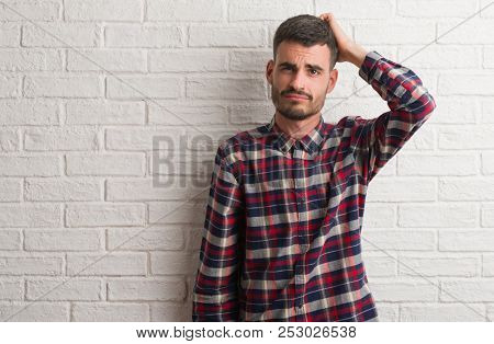 Young adult man standing over white brick wall confuse and wonder about question. Uncertain with doubt, thinking with hand on head. Pensive concept.