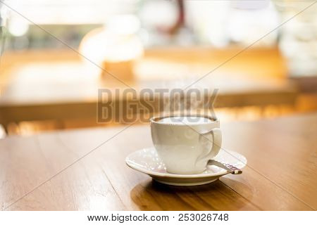 Hot Cup Of Coffee Or Hot Cappuccino On Wooden Table At Coffee Shops In Blurry Background And Golden
