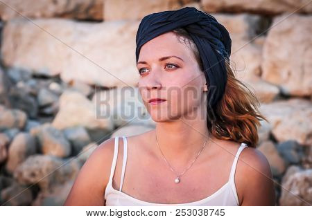 Beautiful Caucasian Young Woman With A Black Shawl On Her Head Looking At The Sunset With Stone Wall