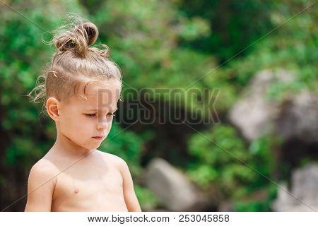 Little Serious Boy Standing On The Beach