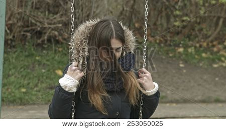 Portrait of young depressed woman in a city park, sit on swing, while close her eyes sadly